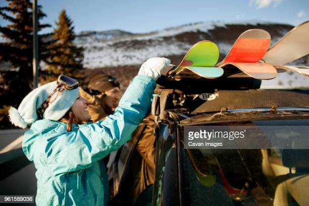 side view of woman removing skis from car while standing by friend at ski resort - ski wear stock pictures, royalty-free photos & images