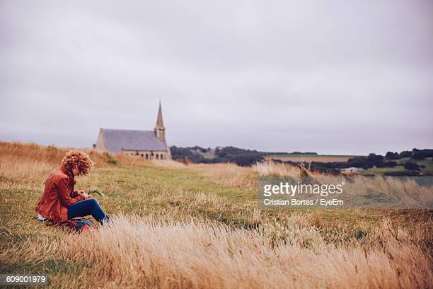 side view of woman resting in grassy field - bortes cristian stock-fotos und bilder