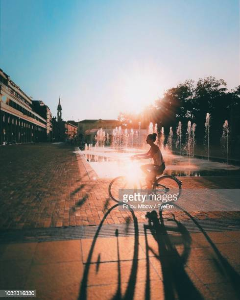 side view of woman riding bicycle on street in city at sunset - femme fontaine photos et images de collection