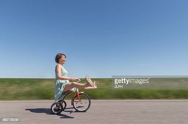 side view of woman riding tricycle in rural area - tricycle stock pictures, royalty-free photos & images