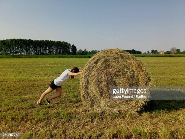 Side View Of Woman Rolling Hay Bale On Field Against Sky