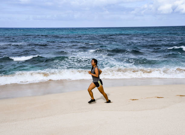 Side View Of Woman Running On Shore At Beach, HaleIwa, United States