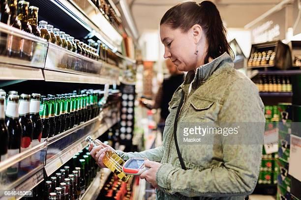 Side view of woman scanning beer bottle in supermarket