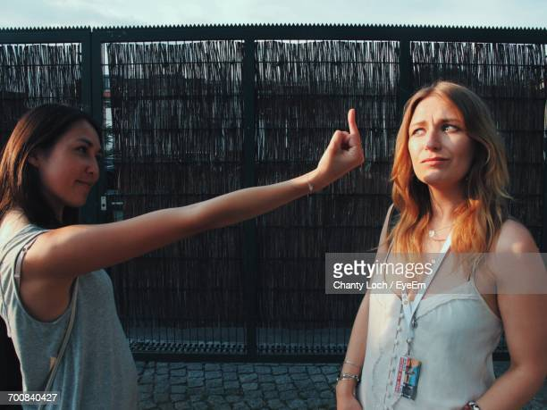 Side View Of Woman Showing Obscene Gesture To Her Friend While Standing Outdoors