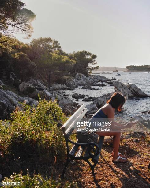 Side View Of Woman Sitting And Using Phone By Lake