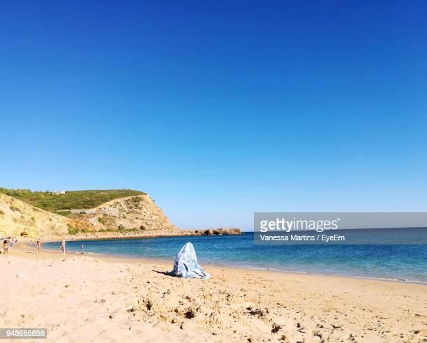 side view of woman sitting at beach against clear blue sky - vanessa martins stock pictures, royalty-free photos & images