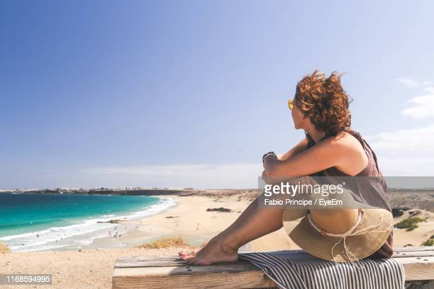 side view of woman sitting at beach against sky - spain stock pictures, royalty-free photos & images