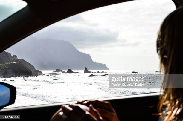 Side View Of Woman Sitting In Car At Beach Against Sky