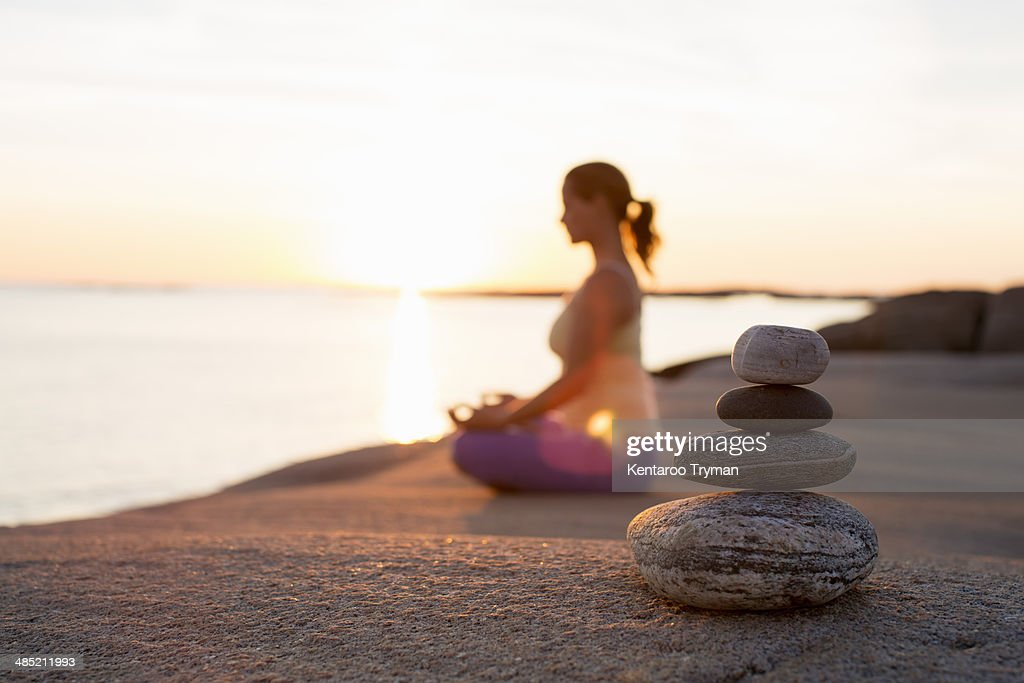 Side view of woman sitting in lotus position on lakeshore with focus on stack of stones : Stock Photo