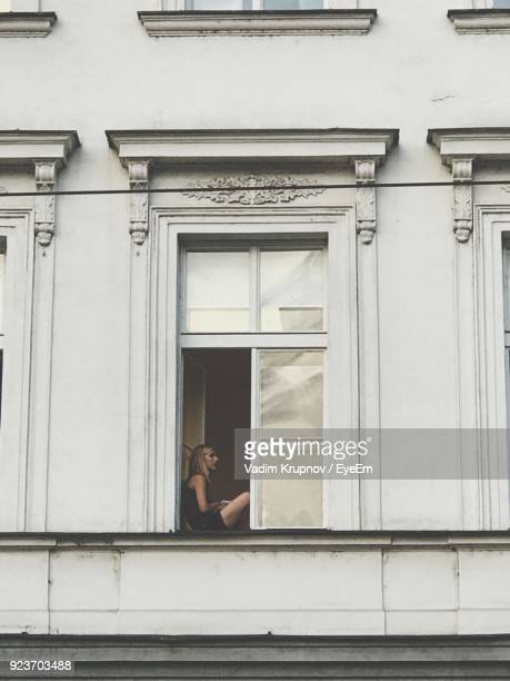 Side View Of Woman Sitting On Apartment Window