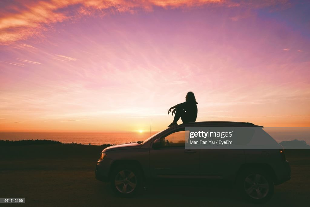Side View Of Woman Sitting On Car Against Sky During Sunset : Stock Photo