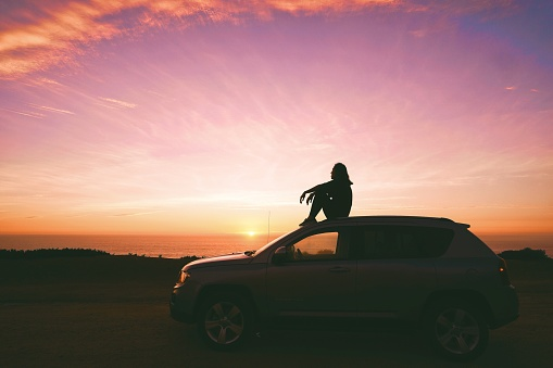 Side View Of Woman Sitting On Car Against Sky During Sunset - gettyimageskorea