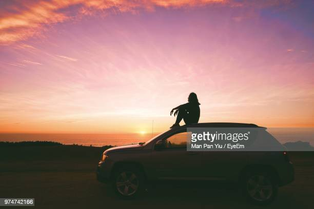 side view of woman sitting on car against sky during sunset - sonnenuntergang stock-fotos und bilder