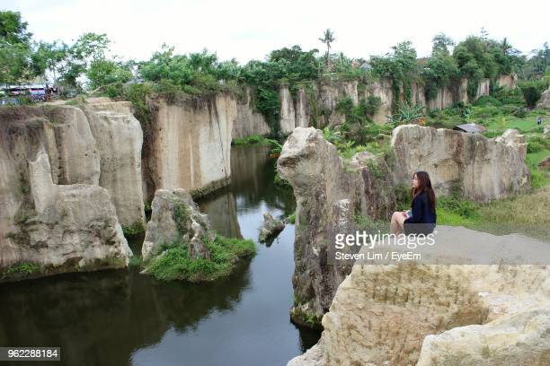 Side View Of Woman Sitting On Cliff By River