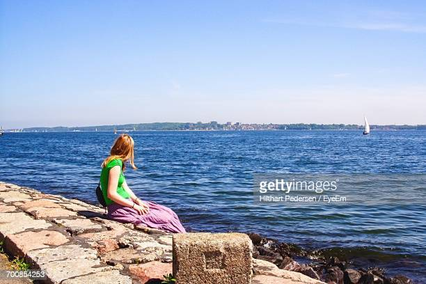 Side View Of Woman Sitting On Groyne In Sea Against Clear Sky