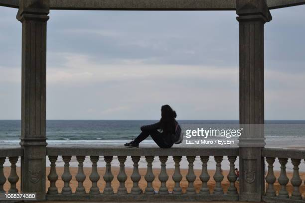 side view of woman sitting on railing at beach against sky - muro stock photos and pictures
