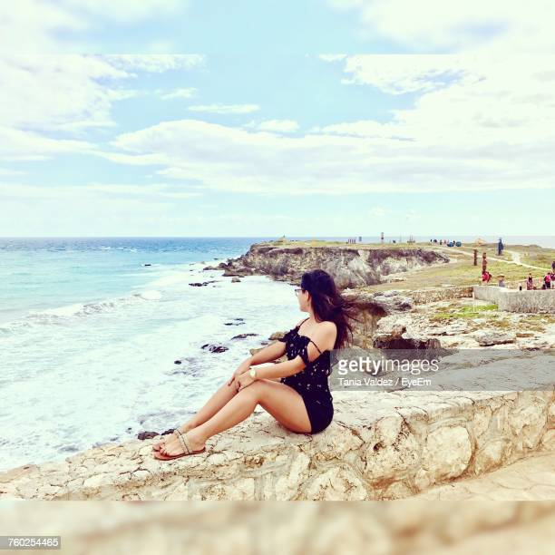 side view of woman sitting on retaining wall at beach in isla mujeres - isla mujeres stock photos and pictures