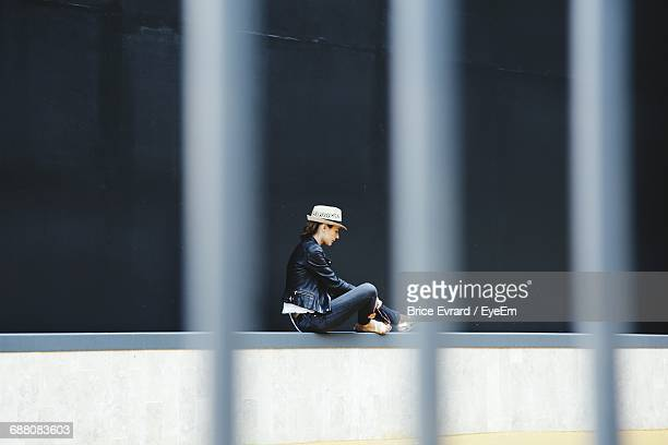 Side View Of Woman Sitting On Retaining Wall Seen Through Fence