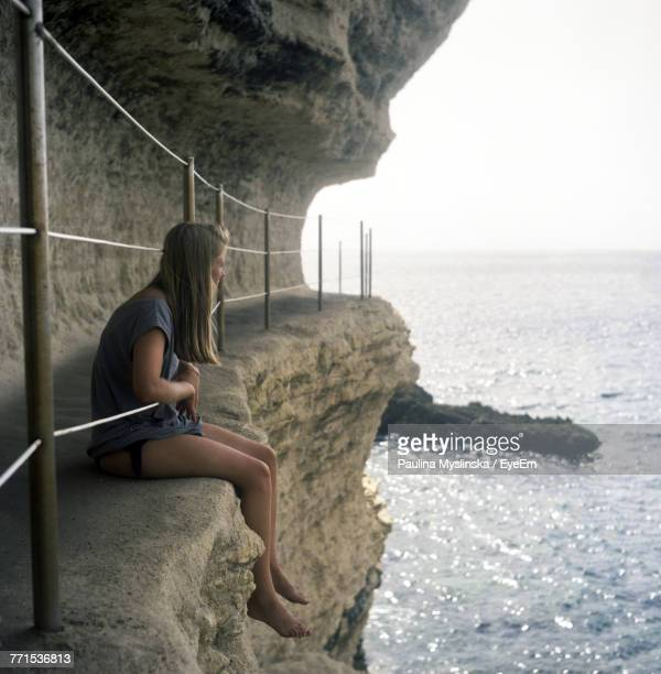 Side View Of Woman Sitting On Rock At Beach