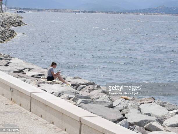 Side View Of Woman Sitting On Rocks By Sea