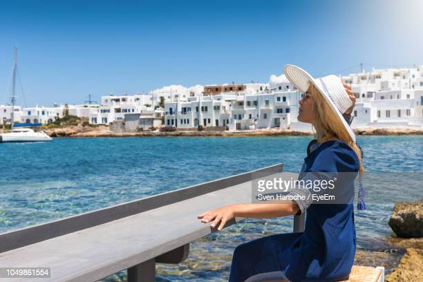 side view of woman sitting on seat on shore against clear blue sky - islas griegas fotografías e imágenes de stock