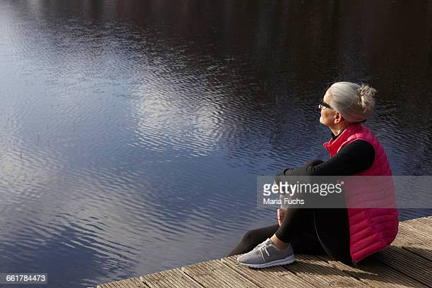 side view of woman sitting on wooden pier looking away - 足を組む ストックフォトと画像