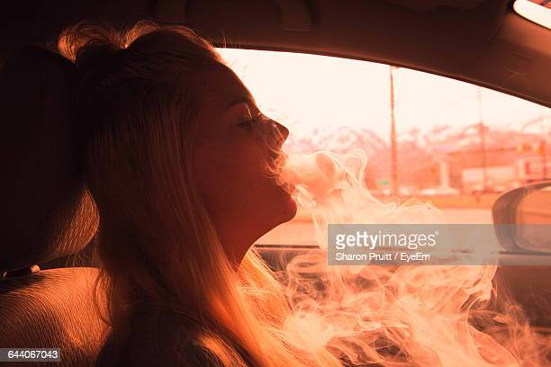 Side View Of Woman Smoking In Car