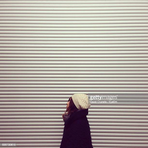 Side View Of Woman Standing Against Closed Shop