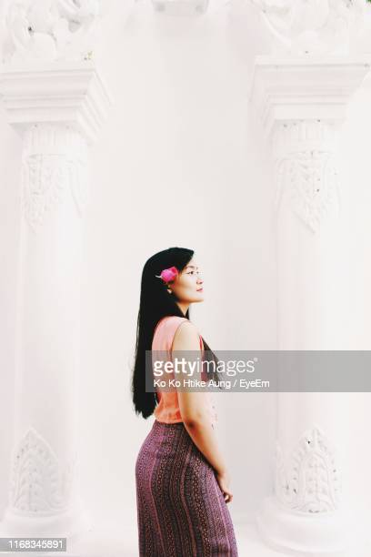side view of woman standing against wall - ko ko htike aung stock pictures, royalty-free photos & images