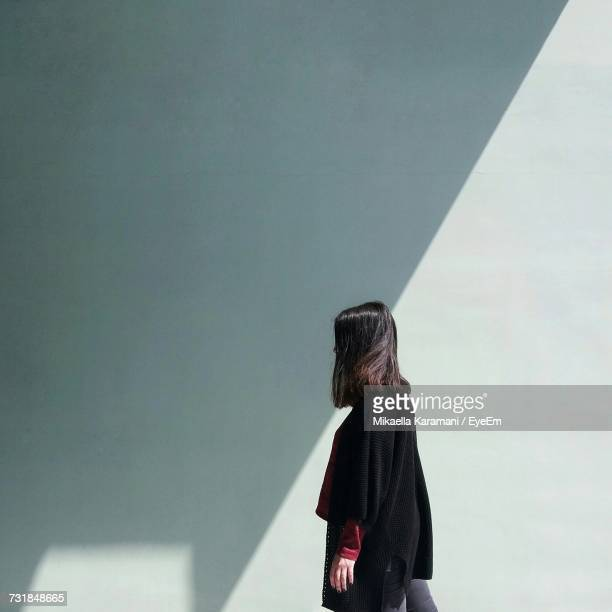 side view of woman standing against wall - shadow stock pictures, royalty-free photos & images