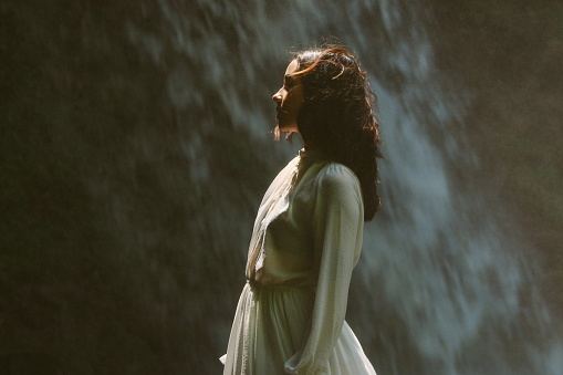 Side View Of Woman Standing Against Waterfall - gettyimageskorea
