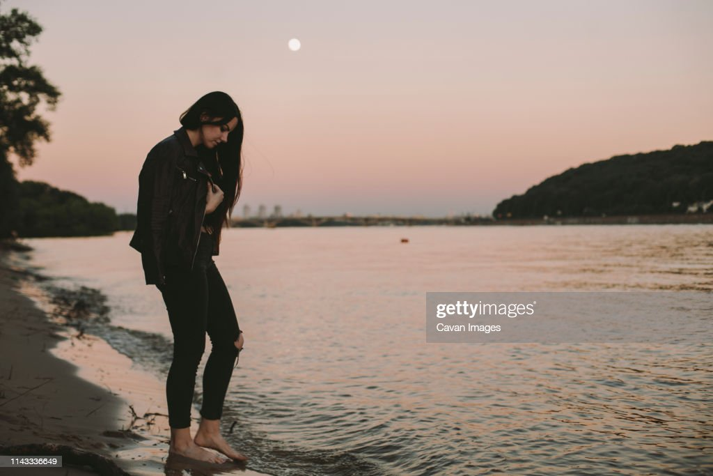 Side view of woman standing at beach against clear sky during sunset : Stock Photo