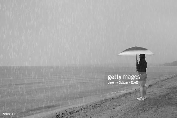 Side View Of Woman Standing At Beach Holding Umbrella On Rainy Day