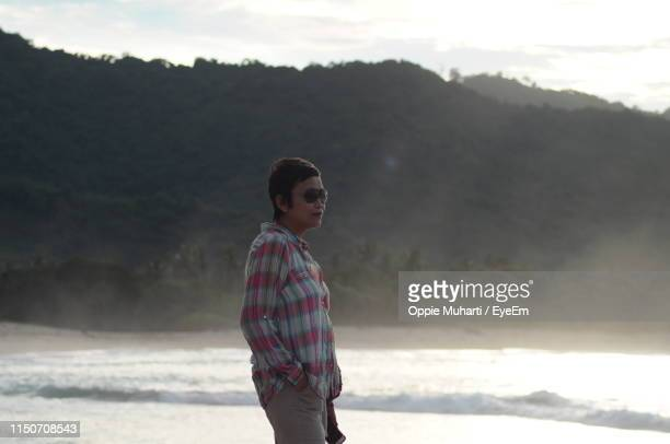 side view of woman standing at beach - oppie muharti stock pictures, royalty-free photos & images