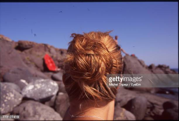 Side View Of Woman Standing At Rocky Beach Against Clear Blue Sky
