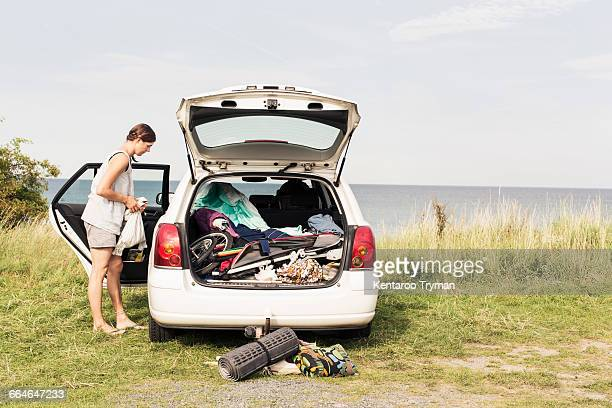 Side view of woman standing by car parked at beach