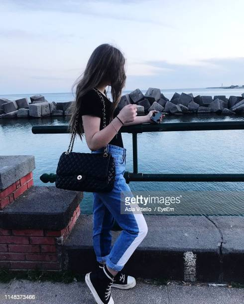 side view of woman standing by railing against sea and sky - one young woman only stock pictures, royalty-free photos & images