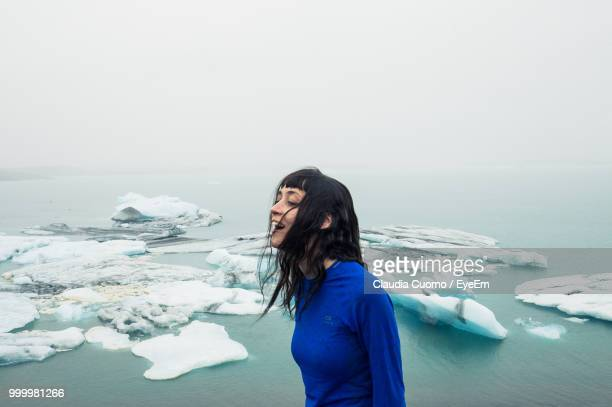 Side View Of Woman Standing By Sea During Winter