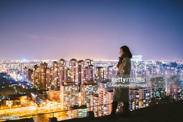 side view of woman standing in front of city - fotostock stock-fotos und bilder