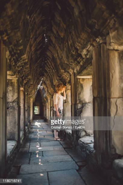 Side View Of Woman Standing In Old Historic Corridor