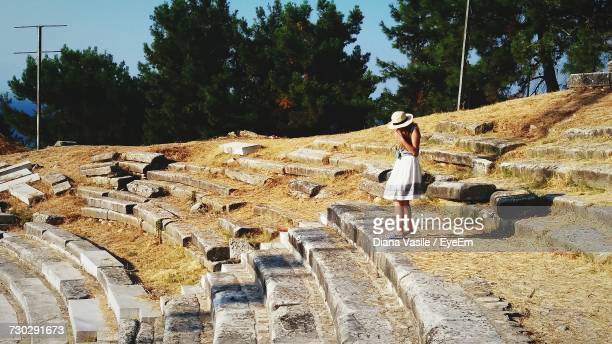 side view of woman standing on broken steps at thasos island - thasos stock photos and pictures