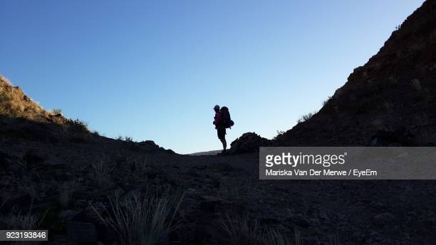 Side View Of Woman Standing On Cliff Against Clear Sky