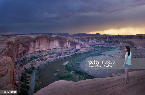 Side View Of Woman Standing On Cliff By River Against Cloudy Sky During Sunset