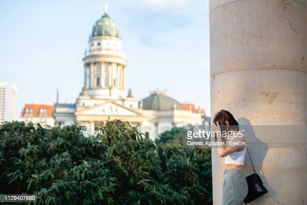 side view of woman standing on column with concert hall in background - konzerthaus berlin stock pictures, royalty-free photos & images