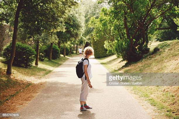 side view of woman standing on country road - bortes foto e immagini stock