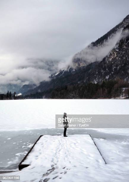 Side View Of Woman Standing On Frozen Lake Against Mountain