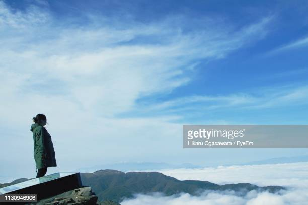 side view of woman standing on mountain against sky - 長野県 ストックフォトと画像