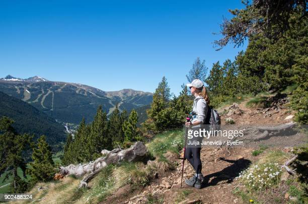 side view of woman standing on mountain while looking at landscape against cloudy sky - andorra stock pictures, royalty-free photos & images