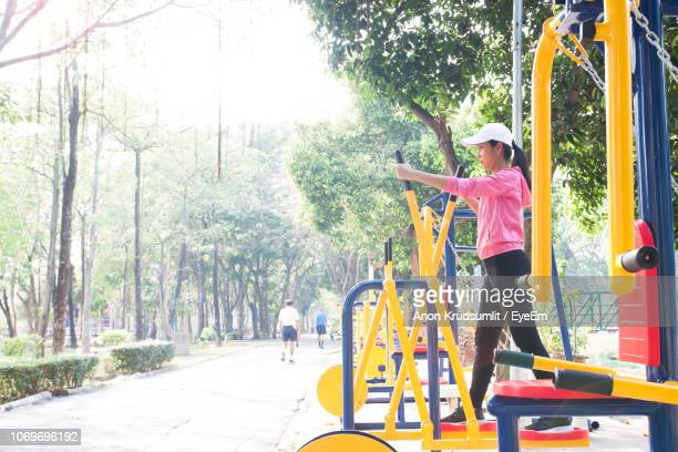 Side View Of Woman Standing On Play Equipment At Park