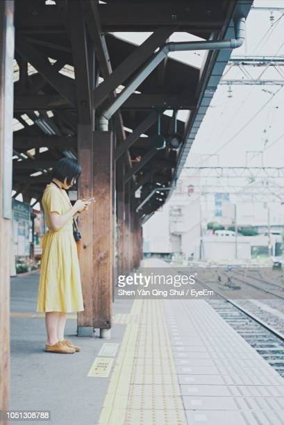 side view of woman standing on railroad station platform - 駅 ストックフォトと画像